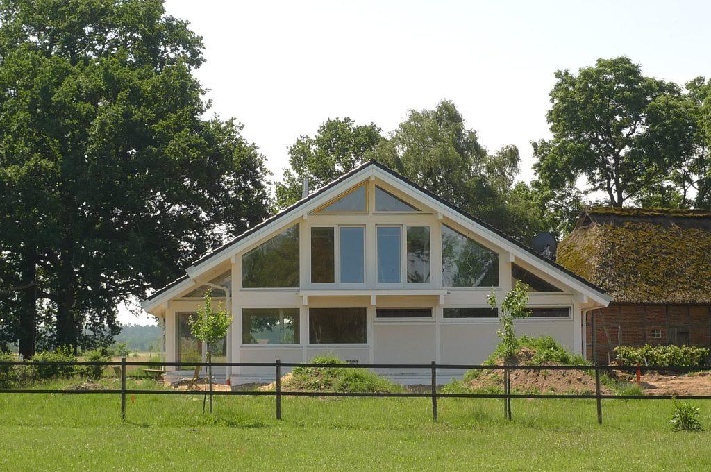 ein modernes Fachwerkhaus in weiß auf grüner Wiese